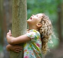 Niña abrazada a un árbol